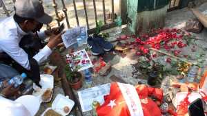 People mourn at the site where a young man died during a protest against the military coup, in Yangon, Myanmar, Sunday, Feb. 28, 2021. (AP Photo)