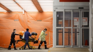 Paramedics wheel a patient into the emergency department at Mount Sinai Hospital in Toronto, Wednesday, Jan. 13, 2021. THE CANADIAN PRESS/Cole Burston