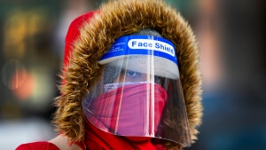A woman bundles up in the cold weather wearing her PPE during the COVID-19 pandemic in Toronto on Thursday, February 11, 2021. THE CANADIAN PRESS/Nathan Denette