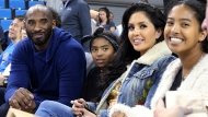 """FILE - In this Nov. 21, 2017, file photo, from left, Los Angeles Lakers legend Kobe Bryant, his daughter Gianna Maria-Onore Bryant, wife Vanessa and daughter Natalia Diamante Bryant are seen before an NCAA college women's basketball game between Connecticut and UCLA, in Los Angeles. Vanessa Bryant says she is focused on """"finding the light in darkness"""" in an emotional story in People magazine. She details how she attempts to push forward after her husband, Kobe Bryant, and daughter Gigi died in a helicopter crash in early 2020. (AP Photo/Reed Saxon, File)"""