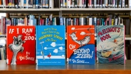 "Dr. Seuss childrens' books, from left, ""If I Ran the Zoo,"" ""And to Think That I Saw It on Mulberry Street,"" ""On Beyond Zebra!"" and ""McElligot's Pool"" are displayed at the North Pocono Public Library in Moscow, Pa., Tuesday, March 2, 2021. Dr. Seuss Enterprises, the business that preserves and protects the author's legacy said Tuesday, that these four titles, as well as ""Scrambled Eggs Super!,"" and ""The Cat's Quizzer,"" will no longer be published because of racist and insensitive imagery. (Christopher Dolan/The Times-Tribune via AP)"