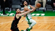 Boston Celtics forward Jayson Tatum, right, is fouled by Toronto Raptors center Aron Baynes on a drive to the basket during the second half of an NBA basketball game, Thursday, March 4, 2021, in Boston. (AP Photo/Charles Krupa)
