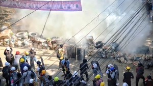 Anti-coup protesters maintain their position behind a barricade despite smoke from tear gas in San Chaung township in Yangon, Myanmar Friday, Mar. 5, 2021. Demonstrators defy growing violence by security forces and stage more anti-coup protests ahead of a special U.N. Security Council meeting on the country's political crisis. (AP Photo)