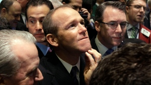 In this Jan. 26, 2011 file photo, then-Nielsen Company CEO David Calhoun, center, watches progress as he waits for the company's IPO to begin trading, on the floor of the New York Stock Exchange. Boeing CEO David Calhoun declined a salary and performance bonus for most of 2020 but still received stock benefits that pushed the estimated value of his compensation to more than $21 million, according to a regulatory filing Friday, March 5, 2021. (AP Photo/Richard Drew, File)