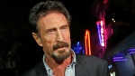 FILE — In this Dec. 12, 2012 file photo, anti-virus software founder John McAfee answers questions to reporters as he walks on Ocean Drive, in the South Beach area of Miami Beach, Fla. McAfee was indicted on fraud and money laundering conspiracy charges alleging that he and cohorts made over $13 million by fooling investors zealous over the emerging cryptocurrency market, authorities said Friday, March 5, 2021. (AP Photo/Alan Diaz, File)