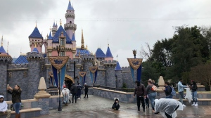 FILE - In this March 13, 2020, file photo, visitors take photos at Disneyland in Anaheim, Calif. California officials will allow people to attend Major League Baseball games and other sporting events, go to Disneyland and watch live performances in limited capacities starting April 1, 2021. The rules announced Friday, March 5, 2021, coincide with baseball's opening day. (AP Photo/Amy Taxin, File)