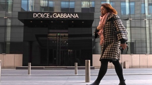 In this Nov. 25, 2018, photo, a woman walks past a Dolce&Gabbana retail outlet in Beijing, China. (AP Photo/Ng Han Guan)