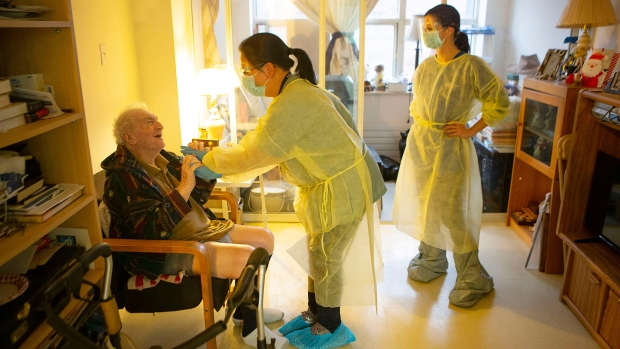 Personal support workers Ana Nguyen, centre, and Olivia Proudfoot tend to Israel Gorlick at Springhurst Manor, part of Parkdale  Assisted Living, a programme run by West Neighbourhood House, in Toronto, Friday, Dec. 4, 2020. THE CANADIAN PRESS/Chris Young