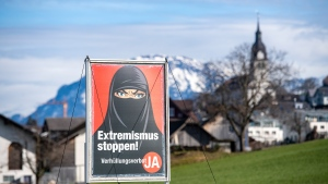A poster supporting the initiative 'Yes to a ban on covering the face' is displayed at the village Buochs, Switzerland, Tuesday, Feb. 16, 2021. At a time when seemingly everyone in Europe is wearing masks to battle COVID-19, the Swiss go to the polls Sunday March 7, 2021, to vote on a long-laid proposal to ban face-coverings like niqabs and burqas worn by some Muslim women or by protesters in ski masks or bandannas. (Urs Flueeler/Keystone via AP)