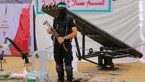 In this July 20, 2016 file photo, a masked Palestinian militant from the Izzedine al-Qassam Brigades, a military wing of Hamas, stands in front of rocket launchers during a weapon exhibition at a Hamas-run youth summer camp, in Gaza City. (AP Photo/Adel Hana, File)
