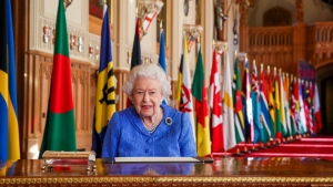 In this photo made available Sunday March 7, 2021, Britain's Queen Elizabeth II poses for a photo while signing her annual Commonwealth Day Message inside St George's Hall at Windsor Castle, England, Friday March 5, 2021. (Steve Parsons/Pool via AP)