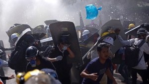Protesters are dispersed as riot police fire tear gas during a demonstration in Yangon, Myanmar, Monday, March 8, 2021. Myanmar security forces continued to clamp down on anti-coup protesters, firing tear gas to break up a crowd of around 1,000 people who were demonstrating in the capital, Naypyitaw. The protesters deployed fire extinguishers to create a smoke screen as they fled from authorities. (AP Photo)