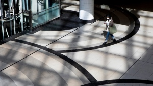 A woman wears a mask as she walks through Toronto's Eaton Centre Shopping mall, on Saturday March 21, 2020. THE CANADIAN PRESS/Chris Young
