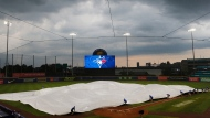 Toronto Blue Jays grounds crew members roll out a tarp to protect the field from rain during the fourth inning of a baseball game against the Tampa Bay Rays, Saturday, Aug. 15, 2020, in Buffalo, N.Y. (AP Photo/Jeffrey T. Barnes)