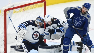 Winnipeg Jets goaltender Connor Hellebuyck (37) makes a pad save as Toronto Maple Leafs centre John Tavares (91) and Jets defenceman Josh Morrissey (44) battles for the loose puck during third period NHL hockey action in Toronto on Tuesday, March 9, 2021. THE CANADIAN PRESS/Nathan Denette