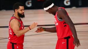Toronto Raptors guard Fred VanVleet (23) and forward Pascal Siakam (43) virtually shake hands before the team's NBA basketball game against the Orlando Magic on Wednesday, Aug. 5, 2020, in Lake Buena Vista, Fla. (Kim Klement/Pool Photo via AP)