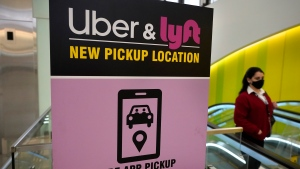 FILE - In this Feb. 9, 2021 file photo, a passer-by walks past a sign offering directions to an Uber and Lyft ride pickup location at Logan International Airport, in Boston. Uber and Lyft have teamed up to create a database of drivers ousted from their ride-hailing services for complaints about sexual assault and other crimes that have raised passenger-safety concerns for years. (AP Photo/Steven Senne, File)