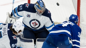 Toronto Maple Leafs centre Auston Matthews (34) gets past Winnipeg Jets centre Mark Scheifele (55) to score the game winning goal on Jets goaltender Connor Hellebuyck (37) during overtime NHL action in Toronto on Thursday, March 11, 2021. THE CANADIAN PRESS/Frank Gunn