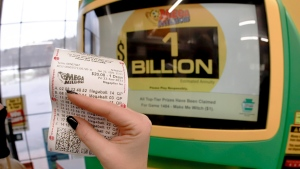 In this Jan. 22, 2021, file photo, a patron, who did not want to give her name, shows the ticket she had just bought for the Mega Millions lottery drawing at the lottery ticket vending kiosk in Cranberry Township, Pa. Four people in a suburban Detroit lottery club have won a $1.05 billion Mega Millions lottery jackpot and will share $557 million after taxes. Officials made the announcement Friday, March 12, 2021, nearly two months after the Jan. 22, drawing. (AP Photo/Keith Srakocic File)