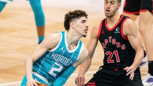 Charlotte Hornets guard LaMelo Ball (2) drives to the basket while guarded by Toronto Raptors guard Matt Thomas (21) during the second half of an NBA basketball game in Charlotte, N.C., Saturday, March 13, 2021. (AP Photo/Jacob Kupferman)