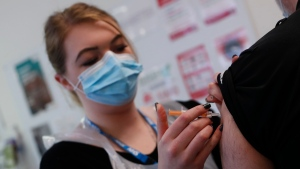 Pharmacy Technician Katrina Bonwick administers a dose of the AstraZeneca COVID-19 vaccine at the Wheatfield surgery in Luton, England, Thursday, March 18, 2021. (AP Photo/Alastair Grant)