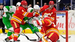 Toronto Maple Leafs' Alex Galchenyuk (12) tries to knock the puck loose from Calgary Flames goaltender Jacob Markstrom (25) as Flames' Rasmus Andersson (4) defends during third period NHL action in Toronto on Friday, March 19, 2021. THE CANADIAN PRESS/Frank Gunn
