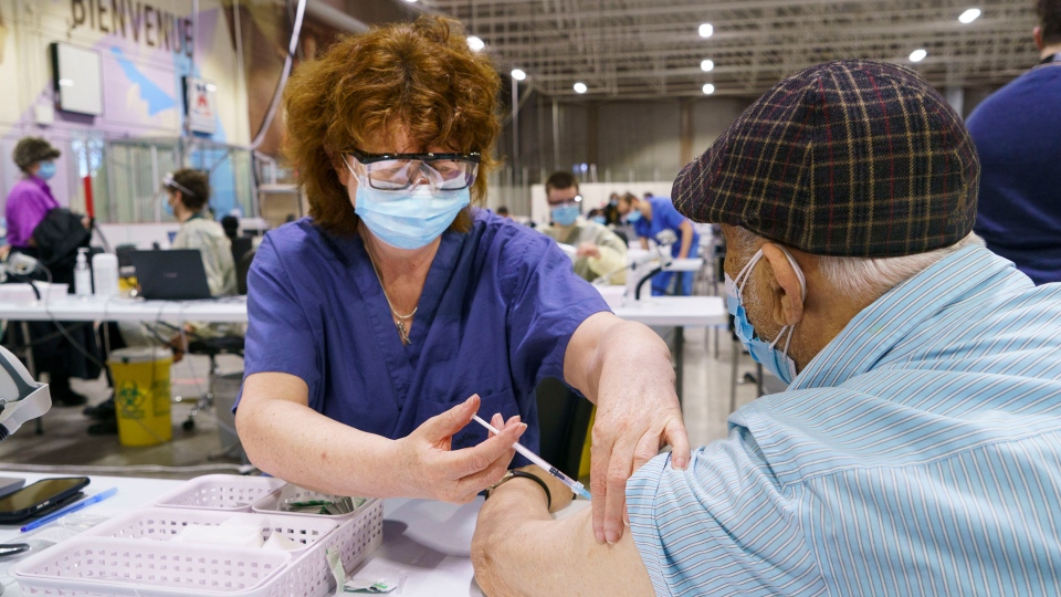 A senior citizen receives a first dose of COVID-19 vaccine at a vaccination clinic in a hockey arena in Montreal, on Wednesday, March 10, 2021. THE CANADIAN PRESS/Paul Chiasson