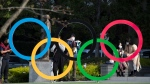People take pictures of the Olympic rings installed by the Japan Olympic Museum in Tokyo on Friday, March 19, 2021. (AP Photo/Hiro Komae)