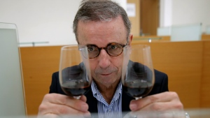Bordeaux Mayor Pierre Hurmic checks glasses of wine, during a tasting session, with one glass containing wine that spent a year orbiting the world in the International Space Station, at the Institute for Wine and Vine Research in Villenave-d'Ornon, southwestern France, Monday, March 1, 2021. Researchers in Bordeaux are carefully studying a dozen bottles of French wine that returned to Earth after a stay aboard the International Space Station. They're releasing preliminary results Wednesday, March 24, 2021. At a one-of-a-kind tasting this month, 12 connoisseurs sampled one of the space-traveled wines, blindly tasting it alongside a bottle from the same vintage that had stayed in a cellar. (AP Photo/Christophe Ena)