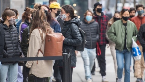 People wear face masks as they wait to enter a store in Montreal, Saturday, March 27, 2021, as the COVID-19 pandemic continues in Canada and around the world. THE CANADIAN PRESS/Graham Hughes