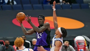 Toronto Raptors forward Pascal Siakam (43) passes the ball between Golden State Warriors guard Nico Mannion (2) and guard Damion Lee (1) during the second half of an NBA basketball game Friday, April 2, 2021, in Tampa, Fla. (AP Photo/Chris O'Meara)
