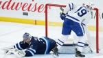 Toronto Maple Leafs' Jason Spezza (19) scores on Winnipeg Jets goaltender Connor Hellebuyck (37) in shootout NHL action in Winnipeg on Friday, April 2, 2021. THE CANADIAN PRESS/John Woods