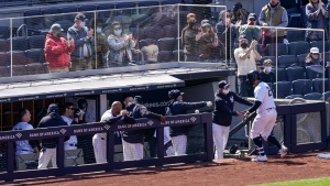New York Yankees' Gary Sanchez (24) celebrates at the dugout as fans cheer behind plastic barriers after hitting a home run during the fourth inning of a baseball game, Saturday, April 3, 2021, in New York. (AP Photo/John Minchillo)