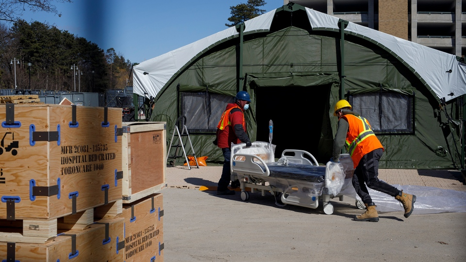 Workers wheel a hospital bed into a field hospital under construction at Sunnybrook Hospital, in Toronto, Sunday, March 14, 2021. THE CANADIAN PRESS/Cole Burston