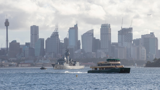 A ferry sails across the Sydney harbour past the HMAS Arunta, an Anzac-class frigate of the Royal Australian Navy, moored in Sydney, Australia, Tuesday, April 6, 2021. New Zealand announced the start date for a long-anticipated travel bubble between Australia and New Zealand that will allow people to travel between the two countries without going through quarantine, allowing families to reunite and giving a big boost to the struggling tourism industry will begin April 19. (AP Photo/Mark Baker)