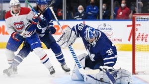 Toronto Maple Leafs goaltender Jack Campbell (36) makes a save as Montreal Canadiens defenceman Alexander Romanov (27) and Maple Leafs defenceman Justin Holl (3) look for the rebound during second period NHL hockey action in Toronto on Wednesday, April 7, 2021. THE CANADIAN PRESS/Nathan Denette