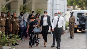 Mrs. World 2020 Caroline Jurie, center, leaves a police station after obtaining bail in Colombo, Sri Lanka, Thursday, April 8, 2021. Jurie's decision to remove the crown from the the winning Mrs. Sri Lanka contestant on stage moments after the winner was announced, because of claims she was a divorcee, drew widespread social media condemnation. The winner Pushpika de Silva who was crowned again later had complained to police that her head was wounded when the clips of her crown were removed by Jurie. (AP Photo/Eranga Jayawardena)
