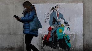 "A woman walks past a poster depicting a scene from the famed movie "" Roman Holiday"" with Gregory Peck and Audrey Hepburn wearing surgical masks as riding a Lambretta scooter in Rome, Friday, April 9, 2021. Italy has seen a stabilizing of the new variant-fueled infections over the past three weeks, though its daily death count remains stubbornly high, averaging between 300-500 COVID-19 victims per day, and its ICU capacity for virus patients is well over the threshold set by the government. (AP Photo/Gregorio Borgia)"
