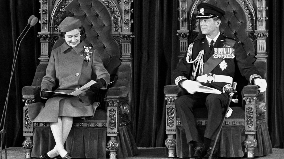 The Queen looks at her program seated next to Prince Philip on thrones from the Senate Chamber on Parliament Hill in Ottawa on April 17, 1982, where they took part in proclaiming Canada's independence from Britain. Prince Philip, the Queen's husband of more than 70 years, passed away at Windsor Castle on Friday, Buckingham Palace announced. THE CANADIAN PRESS/Ron Poling
