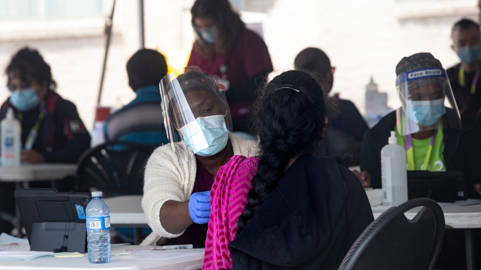 A staff member from Michael Garron Hospital administers a Moderna vaccine at a mobile vaccination site outside the Masjid Mosque in Toronto on Saturday April 10, 2021. THE CANADIAN PRESS/Chris Young