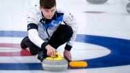 Scotland skip Bruce Mouat, centre, makes a shot against Team Canada in the qualification round at the Men's World Curling Championships in Calgary, Alta., Friday, April 9, 2021.THE CANADIAN PRESS/Jeff McIntosh
