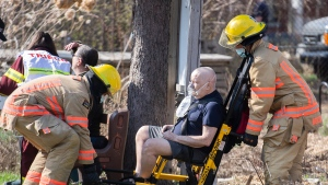 A man receives oxygen after being removed from an apartment building following a fire in Montreal, Sunday, April 11, 2021. THE CANADIAN PRESS/Graham Hughes