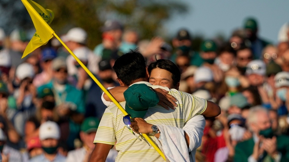 Hideki Matsuyama, of Japan, hugs his caddie Shota Hayafuji after winning the Masters golf tournament on Sunday, April 11, 2021, in Augusta, Ga. (AP Photo/Charlie Riedel)