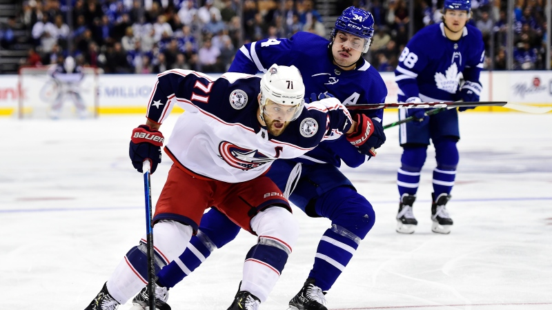 Columbus Blue Jackets left wing Nick Foligno (71) protects the puck from Toronto Maple Leafs centre Auston Matthews (34) during first period NHL action in Toronto on Monday, Oct. 21, 2019. THE CANADIAN PRESS/Frank Gunn