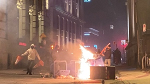 People take part in an anti-curfew protest in Montreal on Sunday April 11, 2021. Hundreds of people gathered in Old Montreal tonight in defiance of a new 8 p.m. curfew. THE CANADIAN PRESS/Giuseppe Valiante