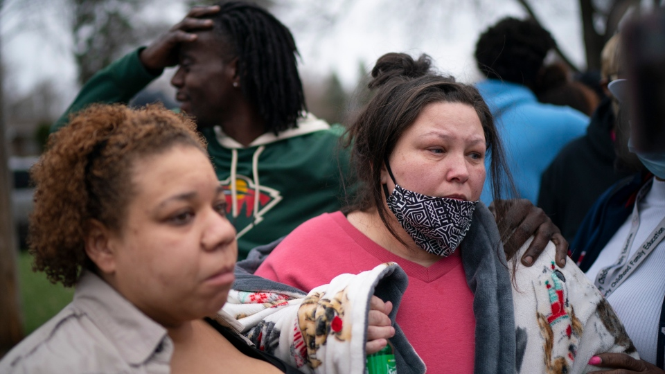 Friends and family comfort Katie Wright, right, while she speaks briefly to news media near where the family says her son Daunte Wright, 20, was shot and killed by police Sunday, April 11, 2021, in Brooklyn Center, Minn. (Jeff Wheeler/Star Tribune via AP)