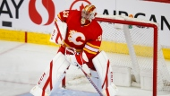 Calgary Flames goalie David Rittich passes the puck during first period NHL hockey action against the Winnipeg Jets, in Calgary, Alta., Saturday, March 27, 2021. THE CANADIAN PRESS/Todd Korol