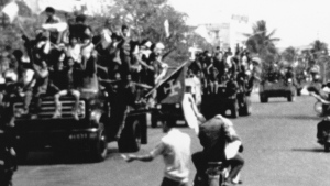 Flag waving and jubilating Red Khmer soldiers enter the city of Phnom Penh on their trucks, April 17, 1975, when this Cambodian capital surrendered to the Khmer Rouge. Civilians pass the truck convoy on their motor scooters. (AP Photo)