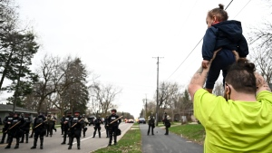 Damik Wright, brother of Daunte Wright, who the family said was shot and killed earlier Sunday by police, holds Daunte's son Daunte Jr., over his head to look at police officers assembling with riot gear at 63rd Avenue North and Lee Avenue North, Sunday, April 11, 2021, in Brooklyn Center, Minn. (Aaron Lavinsky/Star Tribune via AP)