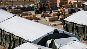 Workers uncrate hospital beds at a field hospital under construction at Sunnybrook Hospital, in Toronto, Sunday, March 14, 2021. THE CANADIAN PRESS/Cole Burston